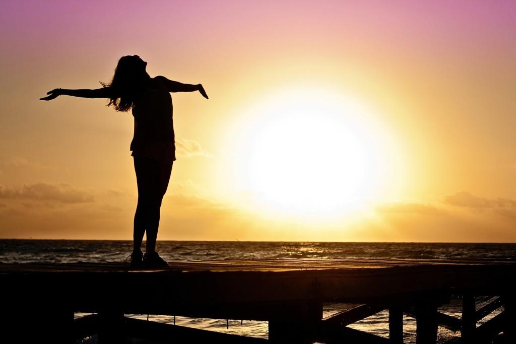 太陽を背景に女性が両手を広げている影